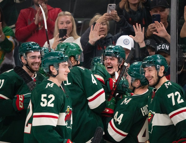 A bloodied Minnesota Wild center Adam Beckman (53) celebrated his game-winning overtime goal with teammates.