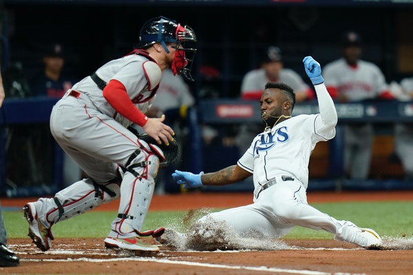 Tampa Bay Rays' Randy Arozarena scores a run in the first inning against Boston Red Sox catcher Christian Vazquez