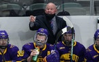 Minnesota State head coach Mike Hastings, back, directs his team against Minnesota in the second period of an NCAA College Hockey Regional Final, Sund