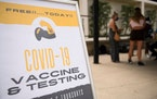 Free COVID-19 vaccine and testing signage is displayed during a public health mobile vaccination clinic at the California State University Long Beach