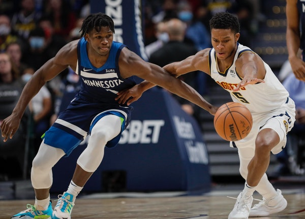 Wolves forward Anthony Edwards and Nuggets guard P.J. Dozier reached for the ball in the first quarter Friday night in Denver.