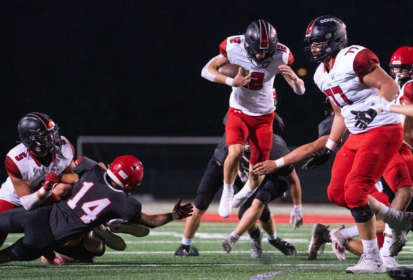 Shakopee quarterback Leyton Kerns (12) leaped over Eden Prairie defenders as he scrambled in the first half. ]