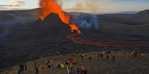 People watch as lava flows from an eruption from the Fagradalsfjall volcano on the Reykjanes Peninsula in southwestern Iceland on May 11, 2021.