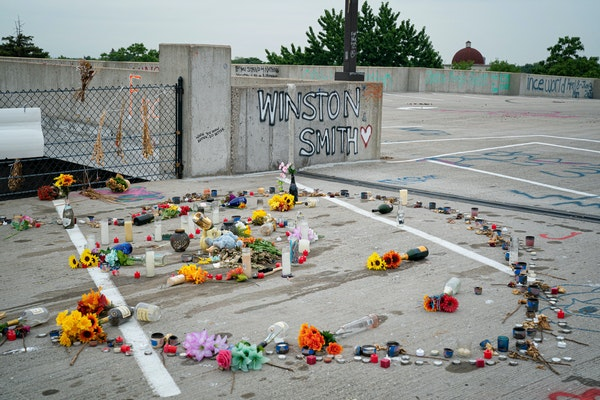 Dead flowers, candles, and makeshift memorials still hung in the parking ramp where Winston Smith was shot and killed. They were expected to be remove