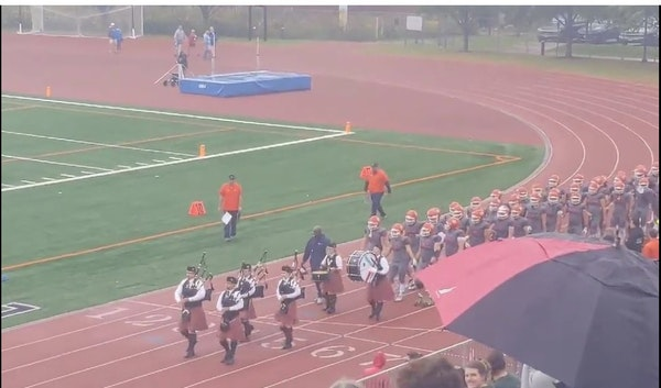 Macalester coach KiJuan Ware leads his team on to the field with the school's bagpipe band