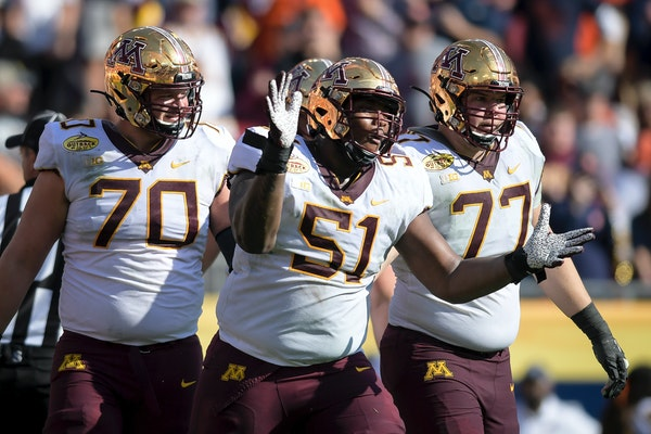Offensive guard Curtis Dunlap Jr. (51) celebrated with Sam Schlueter (70) and Blaise Andries (77) after the Gophers scored a touchdown against Auburn