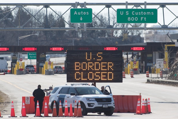 US Customs officers stand beside a sign saying that the U.S. border is closed at the U.S./Canada border in Lansdowne, Ontario, in March 2020.