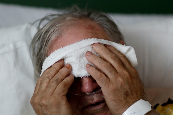 A man places a cold compress on his forehead while battling the flu at a hospital in Georgia.