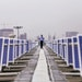 A security guard stands between solar panels implemented by Amplus Solar on the roof of the Yamaha Motor Co. plant in Surajpur, Uttar Pradesh, India,