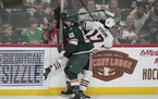 Minnesota Wild right wing Brandon Duhaime (65) crashed into the boards with Chicago Blackhawks center Dylan Strome (17) in the second period.   ] RE