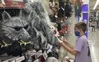 A young customer looks at a Halloween mask at a Party City store, Wednesday, Oct. 6, 2021, in Miami.
