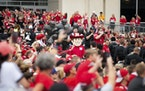 Herbie Husker joins Nebraska fans as they crowd together to watch players arrive at Memorial Stadium