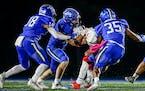 Minnetonka defender Ashton Hoffman (13) and teammates Casey Miller (8) and Prentice Wheatley (35) take down Centennial quarterback Daylen Cummings (12