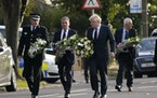 British Prime Minister Boris Johnson and Leader of the Labour Party Sir Keir Starmer, second from left, carry flowers as they arrive at the scene wher