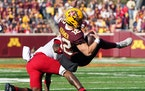 Minnesota Golden Gophers quarterback Cole Kramer (12) was briefly airborne after a run in the first quarter.