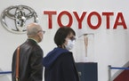 People walk past the logo of Toyota at a showroom in Tokyo, Monday, Oct. 18, 2021.