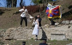 Police officers run to detain protesters displaying a Tibetan flag and a banner disrupting the lighting of the Olympic flame at Ancient Olympia site,