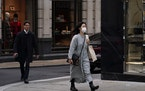 A woman wears a face mask as she walks in London, Tuesday, Oct. 19, 2021. Many scientists are pressing the British government to re-impose social rest