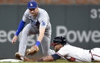 Atlanta Braves' Eddie Rosario dives into second base ahead of the tag by Los Angeles Dodgers second baseman Trea Turner off a pop out by Freddie Freem