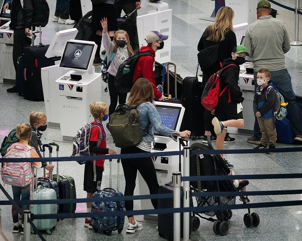 Families with school-age children make their way through Terminal 1 on Tuesday at Minneapolis-St. Paul International Airport. A long weekend of teache