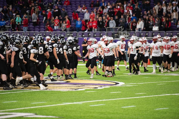 The Blooming Prairie Awesome Blossoms shake hands with the BOLD Warriors after the class A championship game of Prep Bowl XXXVIII at U.S. Bank Stadium