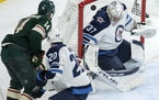 Joel Eriksson Ek (14) scores a goal past Winnipeg Jets goalie Connor Hellebuyck (37) during the first period Tuesday, Oct. 19 at Xcel Energy Center in