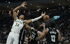 Bucks' forward Giannis Antetokounmpo (34) reached for a rebound during the first half against the Nets.