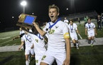 Edina midfielder Ryan Swanda (12) and defender Jackson Holley (14) run with their trophy toward the student section following their 3-2 penalty kick v