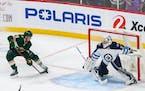 Minnesota Wild center Joel Eriksson Ek (14) takes the game winning shot in overtime on Winnipeg Jets goaltender Connor Hellebuyck (37) to lift the Min