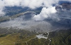 Smoke rises from a crater of Mr. Aso, Kumamoto prefecture, southwestern Japan, Wednesday, Oct. 20, 2021. The volcano erupted Wednesday with a massive