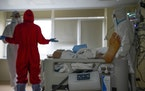 Medics wearing special suits to protect against coronavirus make a briefing as they come to treat a patient with coronavirus at an ICU at the Moscow C