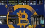 FILE - This May 12, 2021, file photo shows an advertisement for the cryptocurrency Bitcoin displayed on a tram in Hong Kong. Cryptocurrencies have sur