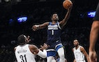 Anthony Edwards (1) drives between Brooklyn Nets' Paul Millsap (31) and Kevin Durant (7) during the first half of a preseason game in New York last