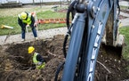 In this Wednesday, April 18, 2018 file photo, Jabaree Broach works as part of a crew digging out and replacing lead service lines in Flint, Mich.