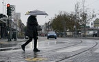 A pedestrian carries an umbrella while crossing a street at Fisherman's Wharf in San Francisco, Wednesday, Oct. 20, 2021.