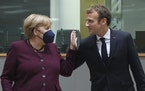 France's President Emmanuel Macron, right, talks to Germany's Chancellor Angela Merkel during a round table meeting at an EU summit in Brussels, F