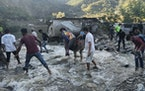 People wade past a flooded area in Dipayal Silgadhi, Nepal, Thursday, Oct. 21, 2021.