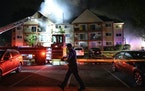 A police officer put up tape as the Fire Department battled a three-alarm blaze at a residential building in north Minneapolis in July.