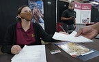 Ariel Jones, a United Parcel Service human resources intern, hands an applicant an information sheet while human resources specialist Mareno Moore mon