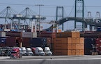 Trucks lined up next to containers at the Port of Los Angeles in San Pedro, Calif.