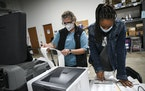 Election judges Kathy Bonnifield, left, and Bretaina Brigham on Friday confirmed the tabulated results from a batch of test ballots fed into a voting