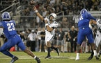 Central Florida quarterback Mikey Keene throws a pass as Memphis linebacker JJ Russell (23) and defensive lineman Morris Joseph (10) defend during the