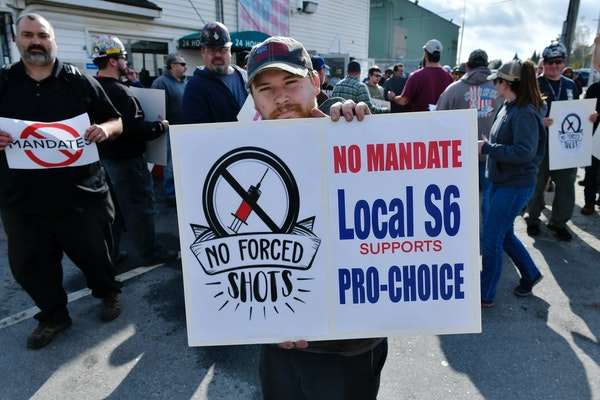 Alec Young, a shipfitter at Bath Iron Works, demonstrated against COVID-19 vaccine mandates outside the shipyard on Friday in Bath, Maine.