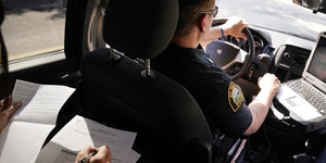 Licensed clinical social worker Amber Ruth, left, took notes on a case as St. Paul Police officer Justin Tiffany drove them to their next call in 2018