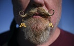 """Scott """"Tundra"""" Hasbrouck, of Thompson, N.D., wears Minnesota earrings in his mustache while tailgating before the start of a football game between"""