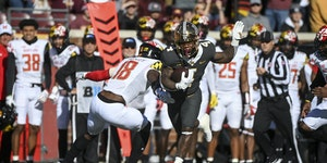 Gophers running back Mar'Keise Irving rushes against Maryland defensive back Jordan Mosley in the first quarter.