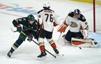 The Wild's Marcus Foligno reaches for a rebound past Anaheim's Josh Mahura after Ducks goalie John Gibson stopped a shot during the first period