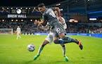 Minnesota United midfielder Emanuel Reynoso jumps around Los Angeles FC forward Raheem Edwards on the end line in the first half