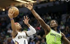 New Orleans Pelicans guard Devonte' Graham shoots against Timberwolves forward Anthony Edwards in the first half.