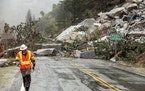 Caltrans maintenance supervisor Matt Martin walks by a landslide covering Highway 70 in the Dixie Fire zone on Sunday, Oct. 24, 2021, in Plumas County